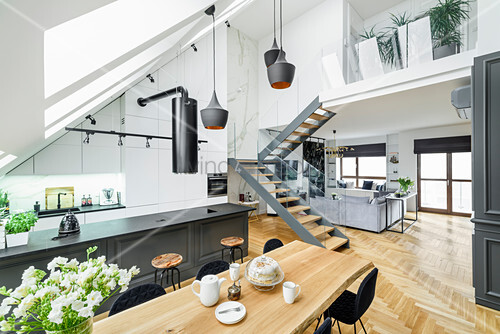 Island counter, dining area and staircase in high-ceilinged room with skylights in sloping wall