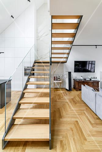 Treppenaufgang mit Glasgeländer als Raumteiler in offenem Wohnraum