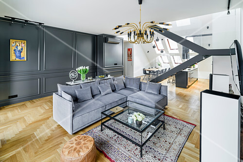 Sofagarnitur und Couchtisch aus Glas in elegantem Wohnraum mit dunkler Kassettenverkleidung