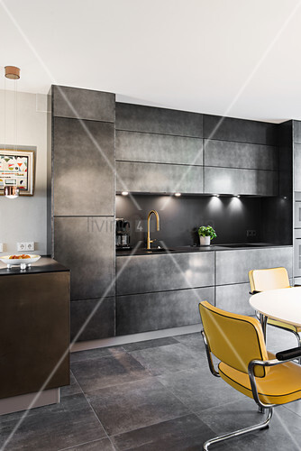 Cantilever chairs in dining area in front of fitted, concrete-effect kitchen