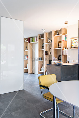 Cantilever chairs in dining area, breakfast bar and floor-to-ceiling wooden shelving in open-plan living space with tiled floor