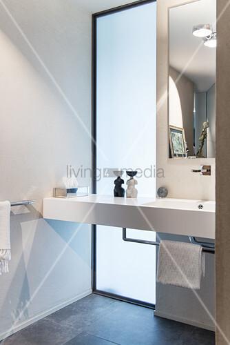 Washstand in front of floor-to-ceiling window in elegant bathroom