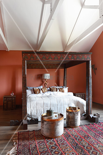 Four-poster bed with artistically carved frame in bedroom