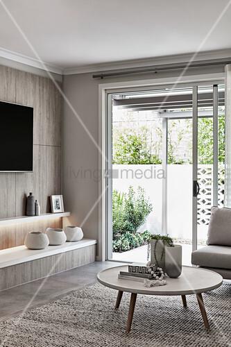 Coffeetable, Wandregale und Fernseher im Wohnzimmer mit Terrassentür