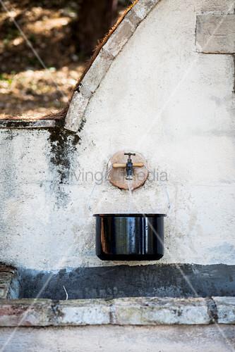 Kochtopf mit Wasser am Steinbrunnen