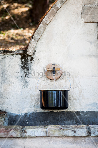 Saucepan below tap of stone fountain
