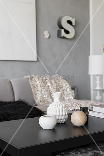 Vases and ornamental spheres on black coffee table in living room in shades of grey