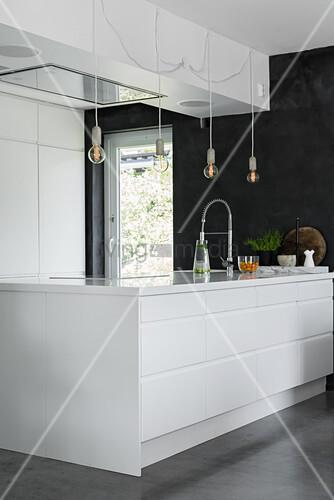 Elegant, white designer kitchen with large island counter
