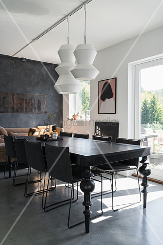 Modern, white pendant lamps above black dining table with turned wooden legs