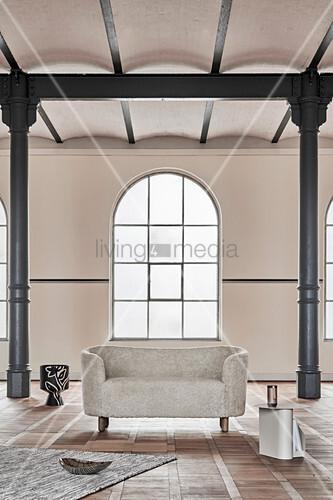 Modernes ovales Sofa in einer alten Fabrikhalle mit Metallsäulen