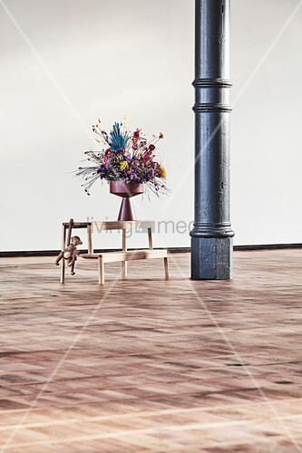 Vase of flowers on bench next to metal pillar