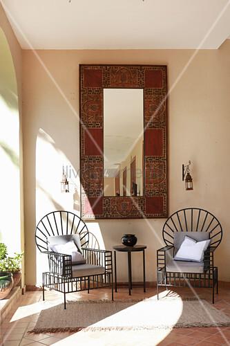 Zwei moderne Metallstühle vorm orientalischen Wandspiegel