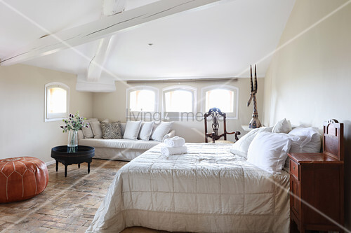 Rustic attic bedroom with wooden ceiling beams