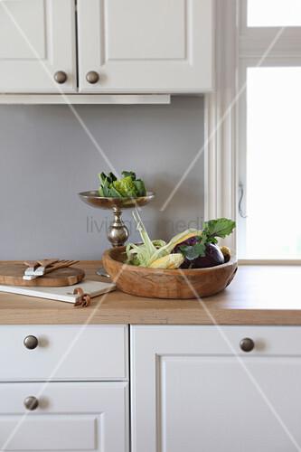 Rustikale Holzschale und silberne Etagere mit Gemüse in der Küche