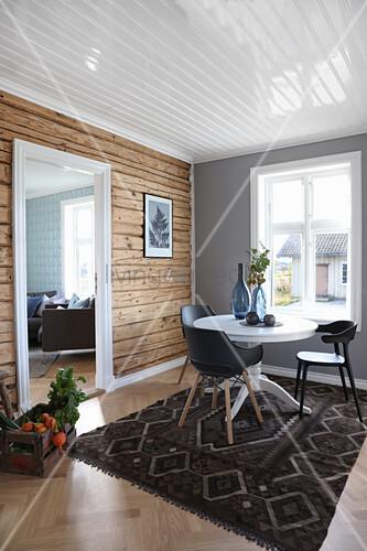 Esszimmer mit Holzwand und Durchgang zum Wohnzimmer