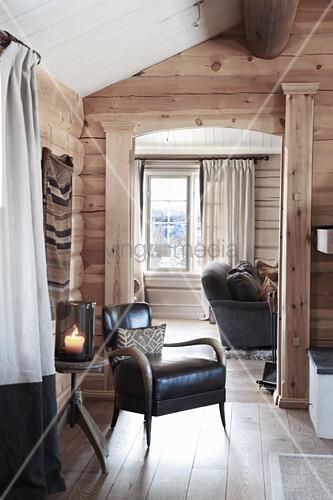 Armchair in front of open doorway leading into living room in wooden house