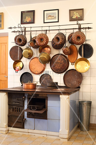 Alter Holzofen, darüber Vintage Pfannen und Backformen in der Küche
