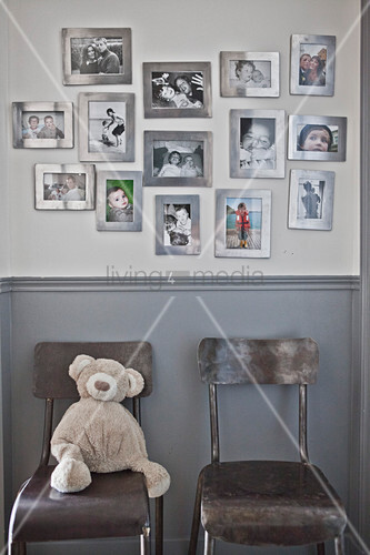 Family photos in silver frames on wall above two chairs