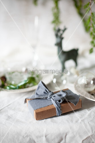 Wrapped present on table set for Christmas meal