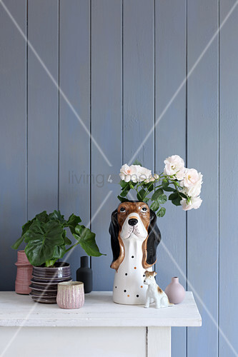 Collection of vases and dog figurines against blue-grey board wall