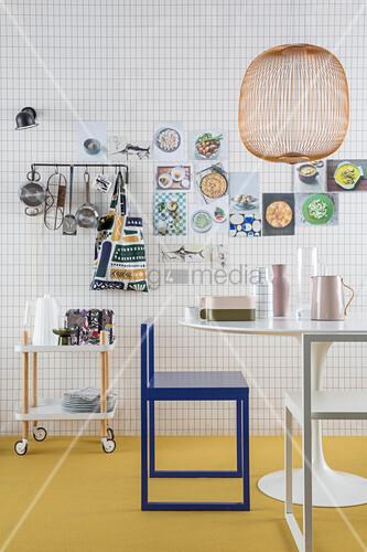 Tapete mit Karoheft-Muster in der Küche, Küchenutensilien an der Wand, Seriverwagen, Tisch und Stuhl