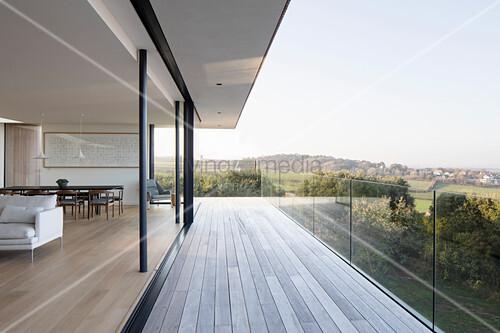 Offener Wohnraum mit geöffneten Glasschiebetüren und Balkon mit Glasbalustrade