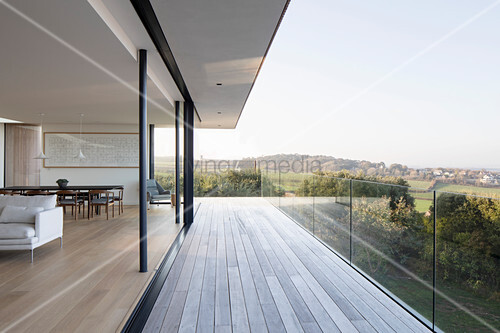 Open-plan interior with open glass sliding wall and balcony with glass balustrade