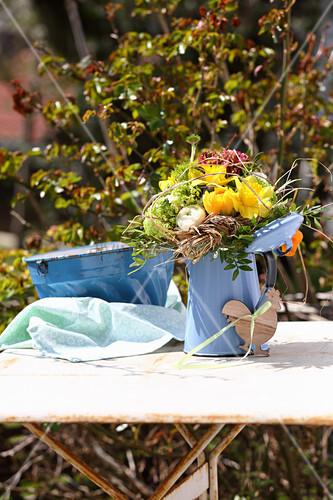 Ländlicher Frühlingsstrauß in einer blauen Emaillekanne