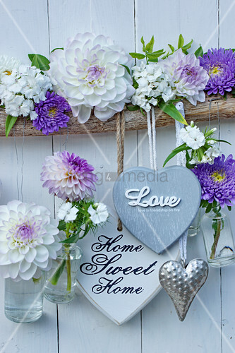 Heart decorations and small suspended bottles holding dahlias and asters