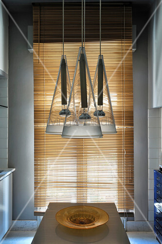 Designer lamps above dining table in open-plan kitchen with louvre blind in background