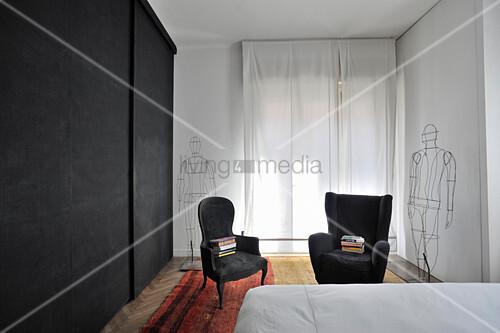 Black wardrobes, black armchair and wire sculptures in bedroom