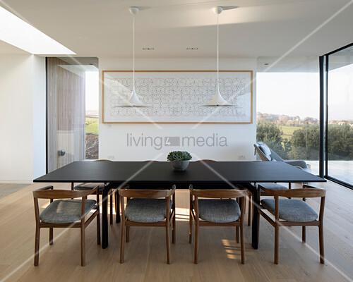 Minimalistischer Essbereich mit dunklem Tisch und Armlehnstühlen
