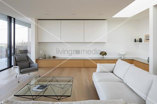 Helle Sofagarnitur, Couchtisch und maßgefertigtes Lowboard vor raumhoher Verglasung in offenem Wohnraum