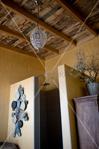 Shower cubicle in bathroom with rustic wooden ceiling