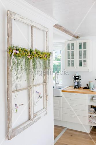 Deko-Fensterrahmen mit Sommergirlande an der Wand