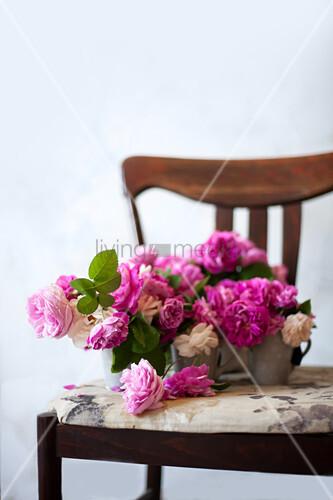 Pink roses in metal vases on chair