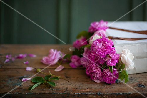 Pink roses in paper bag on wooden table