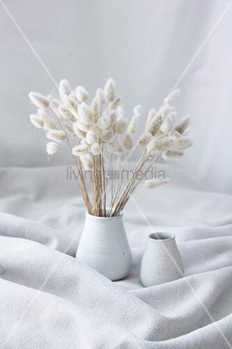 Strauß getrocknetes Samtgras in einer Vase auf gerafftem Stoff