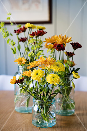 Flowers in shades of yellow and red in glass jars and bottle