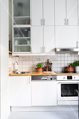 White fitted kitchen with white-tiled splashback