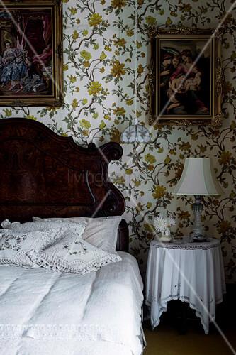 Rustikales Holzbett mit Kissen, Nachttisch und Gemälde an tapezierter Wand im Schlafzimmer