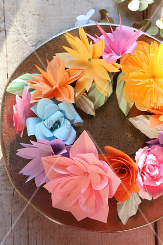 Wreath of colourful paper flowers on plate in sunshine