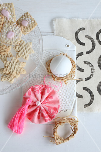 Egg in raffia nest, fabric rosette and pink tassel next to plate of biscuits