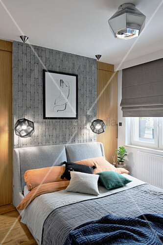 Double bed with grey headboard against grey brick panel in bedroom