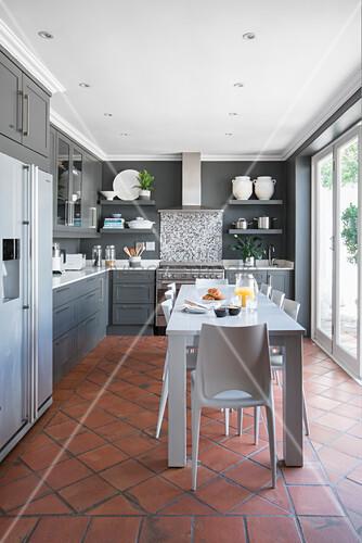 Langer weißer Tisch in der Wohnküche mit Terracottafliesen