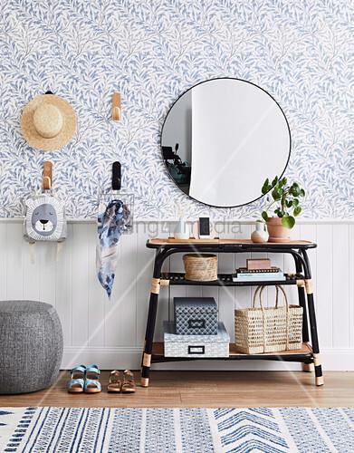 Aufbewahrungsidee in der Diele: Tisch, darüber runder Spiegel und Wandhaken an blau-weißer Tapete