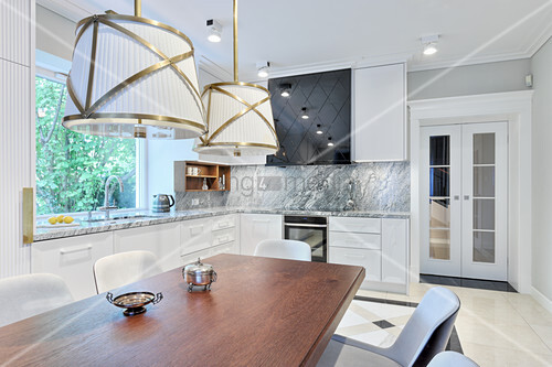 Dark wooden table and white cabinets in elegant kitchen-dining room