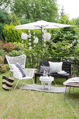 Schwarz-weiße Outdoormöbel, Sonnenschirm und Partydeko in sommerlichem Garten