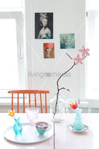 Zweig mit Papierblüten auf dem Tisch mit nostalgischen Vasen