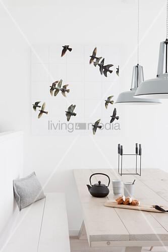 Wanddeko mit Vogelmotiv über dem hellen Holztisch